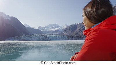 Glacier Bay Alaska cruise ship passenger looking at glacier in Glacier Bay National Park, USA. Woman on travel sailing Inside Passage enjoying view of Johns Hopkins Glacier. RED EPIC SLOW MOTION.