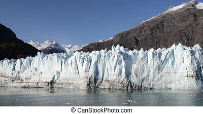 Glacier Bay Alaska cruise vacation travel. Global warming and climate change concept with melting ice. Panning landscape of Margerie Glacier and Mount Fairweather Range mountains.