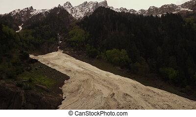 Glacier beneath a jagged mountain ridge - Wide shot tiling...