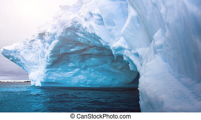 Glacier with natural cave inside swaying on water