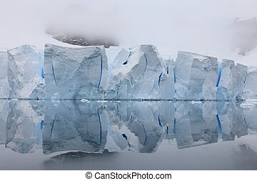Glacier with reflections on water in Antarctica