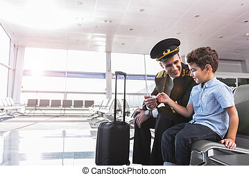 Glad aviator with son in airport - Happy dad pilot is ...
