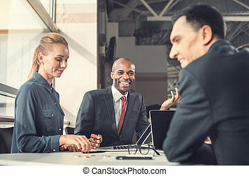 Glad businessman telling with partners