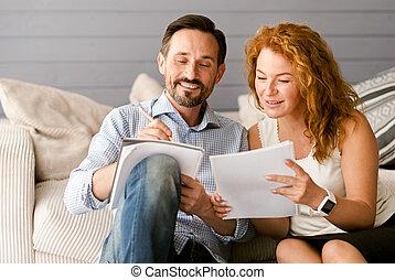 Glad couple enjoying freelance job at home