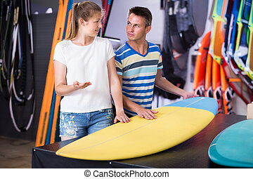 Glad couple is choosing colorful boards