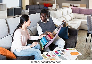 Glad couple is choosing colors for furniture