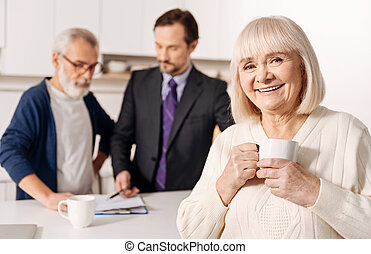 Glad elderly woman relaxing while her husband meeting with lawyer