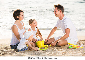 Glad family with two children playing at beach