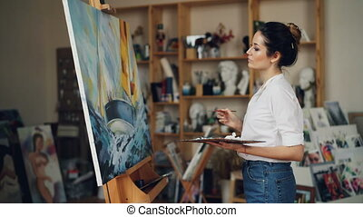 Glad female artist is painting picture depicting boat in sea...