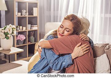 Glad girl hugging granny in room