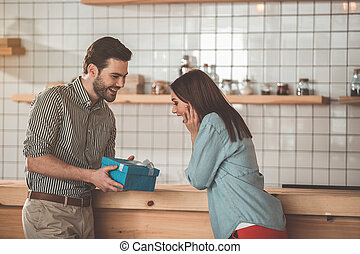 Glad girl receiving gift from boyfriend
