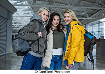 Glad girls posing at the airport with rucksacks