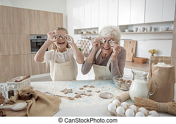 Glad grandmother and child enjoying baking process