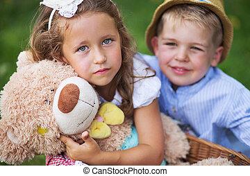 Glad kids holding cute teddy bear