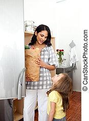 glad, liten flicka, uppackning, speceri väska, med, henne, mor