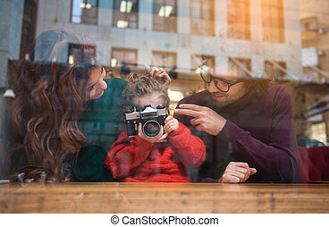 Glad little girl photographing near mother and father