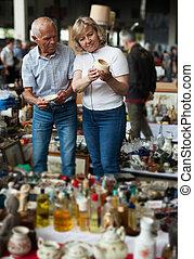 Glad man and woman choosing interesting souvenirs at traditional flea market