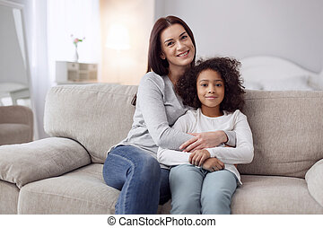 Glad mother and daughter siting on the couch