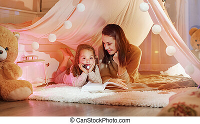 Glad mother reading a novel with her daughter