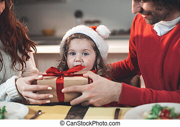 Glad parents holding gift for their little kid