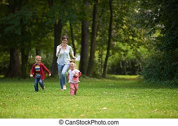 glad släkt, spelande tillsammans, utomhus, i park