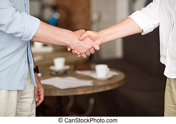 Glad to work together. Pleasant colleagues shaking hands while standing in the cafe