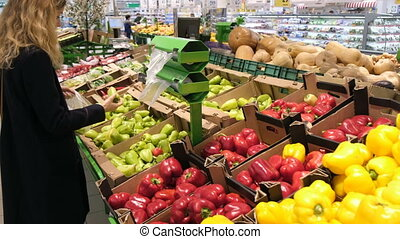 Glad woman choosing green and red paprika in supermarket....