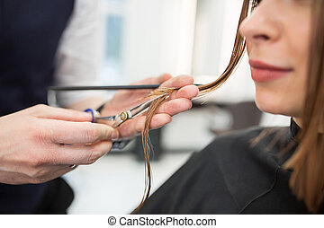 Glad woman having hair cut at hairdresser
