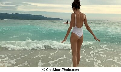 Glad woman in swimsuit splashing in sea waves on tropical...