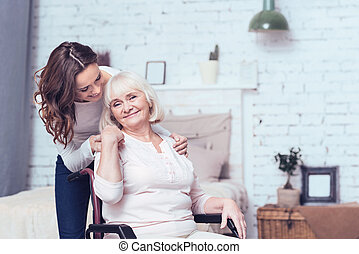 Glad woman taking care of disabled mother on wheelchair