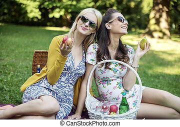 Glad women eating juicy fruit