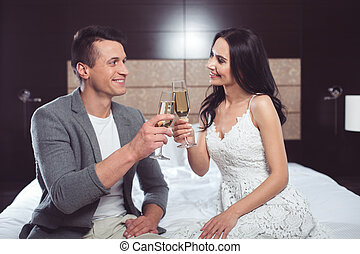 Glad young man and woman clinking glasses of champagne