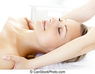 Glad young woman having a massage in a spa center