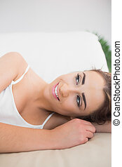 Glad young woman lying on a couch