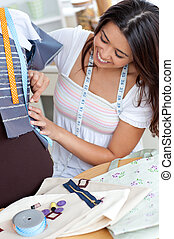 Glad young woman working in a store with clothes