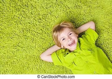 glade, barn, liggende, på, den, grønne, gulvtæppe, baggrund., dreng, smil, og, kigge kamera hos