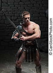 Half length portrait of young attractive warrior gladiator with muscular body posing with sword on dark background. Concept of masculine power, strength