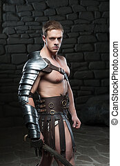 Waistup side view portrait of young attractive warrior gladiator with muscular body posing with sword on dark background. Concept of masculine power, strength
