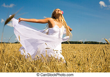 Photo of glad girl with white fabric looking upwards in wheat meadow