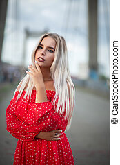 Glamor blonde girl wearing trendy red dress, posing on the bridge in the evening