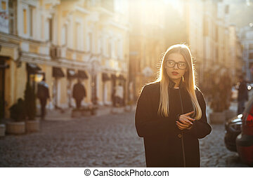 Glamor blonde model with long hair wearing coat, posing in sun glare. Empty space