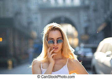 Glamor young girl with long hair wearing glasses, posing at the street in sunny day
