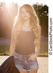 Glamor young model with lush wave hair posing in rays of sun