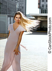 Glamorous blonde blue eyed woman with flying hair wearing pink dress posing in sun glare