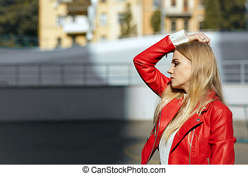 Glamorous blonde model with long hair wearing red leather jacket, posing in rays of sun. Empty space