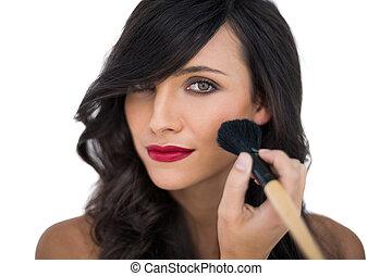 Glamorous brunette applying blusher on her cheek on white background