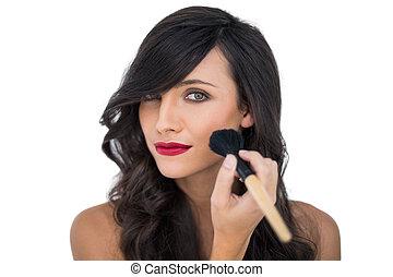 Glamorous brunette applying blusher on white background
