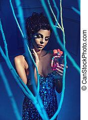 Glamorous brunette beauty holding a bottle of perfum