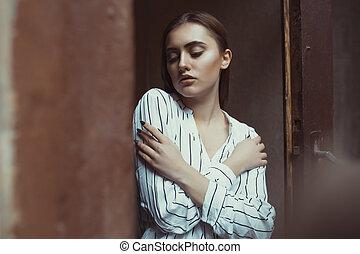 Glamorous brunette model posing in the dark room