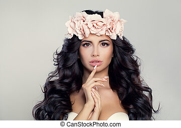 Glamorous Brunette Woman Model with Long Curly Hair, Makeup and Flowers
